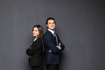 Business man and woman standing back to back isolated on gray background. Teamwork concept Papier Peint