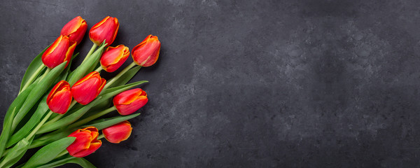 Greeting Card for Mother's or Women's Day. Bouquet of red tulips on a dark stone table. Spring background. Top view. Copy space