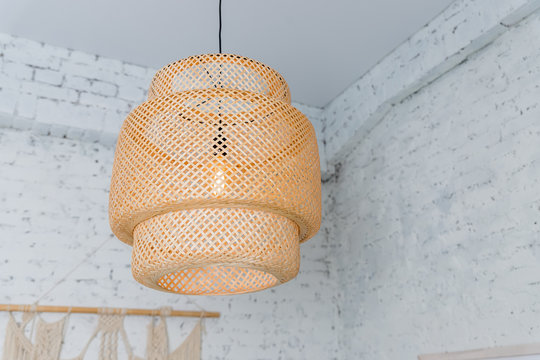 Pendant light with wicker lampshade, rustic style.Wicker shade lamp.Simple home interior with decorative ceiling wicker lamp.Decorating hanging lantern lamps in wooden from bamboo