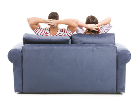 Young couple sitting on sofa against white background, back view