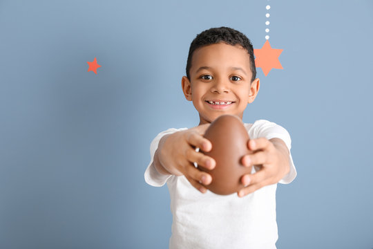 Cute African-American boy with sweet chocolate egg on color background