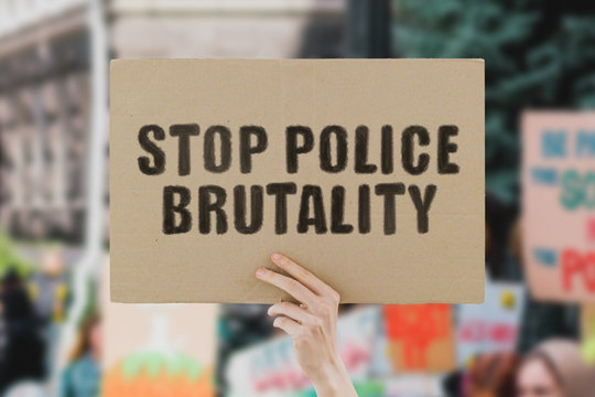 """The phrase """" Stop police brutality """" on a banner in men's hand. Human holds a cardboard with an inscription. Power. Government. Rally. Protest. Crowd. Street. Urban. March. Dictator. People"""