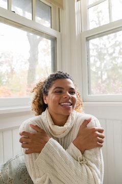 Smiling woman hugging herself