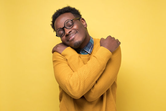 African american man in yellow clothes and glasses hugs himself