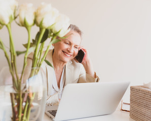 Closeup of senior professional woman using smart phone with laptop at desk (selective focus)