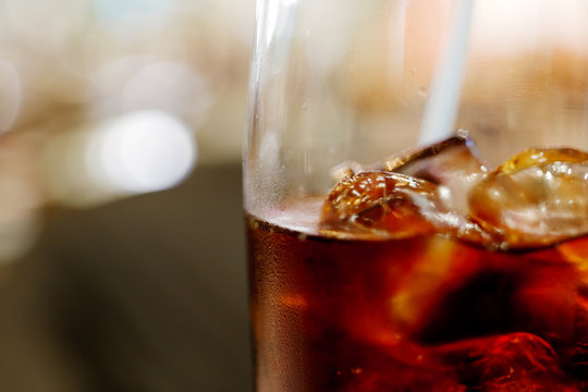 Close up and macro view of cola and ice cube with steam on glass, and blur abstract background of bokeh.