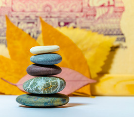 Photo sur Plexiglas Zen pierres a sable Pyramid of sea stones of different colors on a background of leaves.