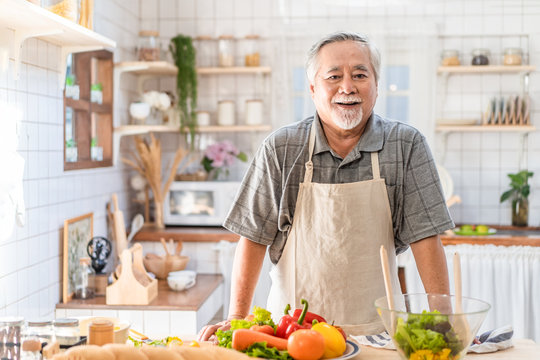 Senior Asian elder man happy living in home kitchen. Grandfather cooking salad dish standing at counter with happiness and smile enjoy retirement life. Older people activity in family at home.