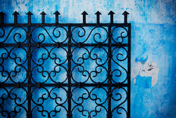 Metal gate against a blue wall in the medina of Rabat, Morocco