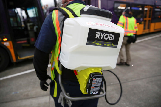 A King County Metro equipment service worker wears a backpack that sprays a Virex solution to sanitize buses against the coronavirus in Seattle