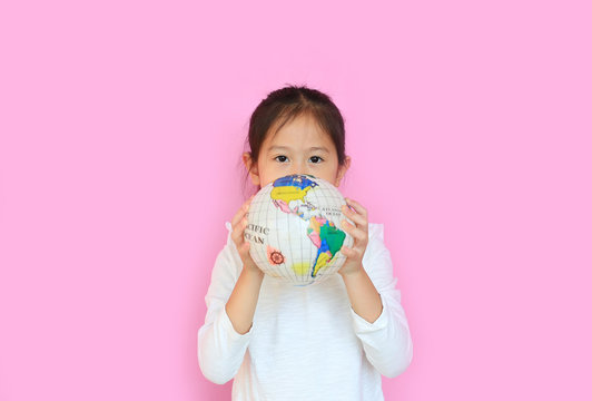 Cute asian little kid girl holding a globe with looking at camera isolated on pink background. Portrait of child with the earth globe sphere. Focus at children face.