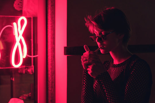 Fashion sexy tomboy hipster short hairstyle woman wear stylish glasses stand near neon street red light sign. Female model adult woman hold smoke cannabis cigarette in city night 80s 90s style glow.