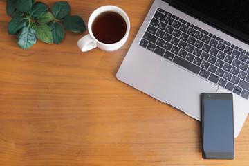 木目のデスクに置かれたノートパソコンとスマホとコーヒーと緑