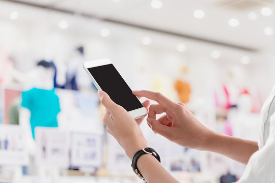 Woman hands holding and using smartphone with blank screen for your text or advertising isolated on blurred shopping mall interior background.Mock up phone mobile concept.