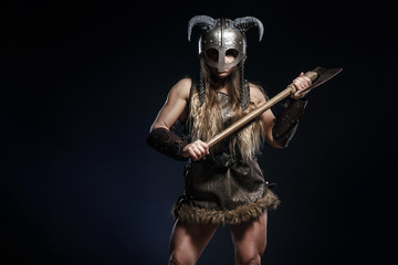 Beautiful female viking woman warrior in battle with big two-handed axe and helmet with horns. Ancient times. Amazon fantasy blonde hair sexy girl. Fototapete