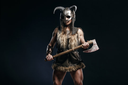 Beautiful female viking woman warrior in battle with big two-handed axe and helmet with horns. Ancient times. Amazon fantasy blonde hair sexy girl.