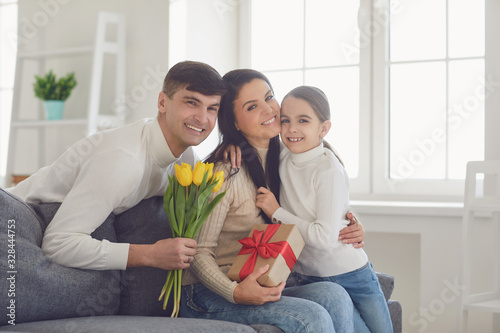 Happy mother's day. Father and baby daughter congratulates mom with flowers and a postcard in a room