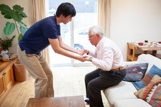 手を握り立ち上がりの介助をする男性介護士