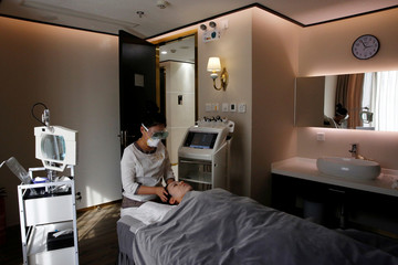 Beautician wearing protective mask and goggles attends to a customer with facial mask during treatment at the Pearl Deluxe beauty spa in Beijing