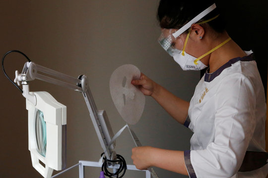 Beautician wearing protective mask and goggles takes out a facial mask during treatment at the Pearl Deluxe beauty spa in Beijing