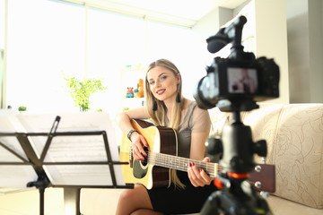 Female Blogger Creating Art Musical Vlog Content. Caucasian Woman Sitting at Living Room Playing Acoustic Guitar. Dreamy Girl Filming Practice Tutorial. Smiling Girl Perform Romance