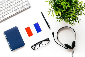 Learn French online. Concept with flag, headset and keyboard on white background top-down