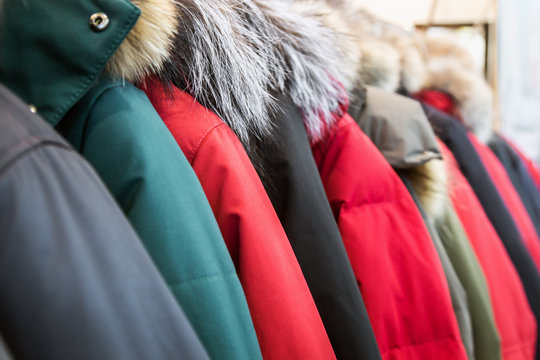 assortment of winter jackets and down jackets on store hangers.
