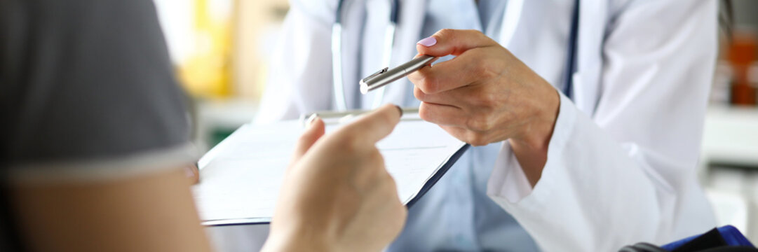 Hand of female GP passing to patient silver pen asking to sign some paper documents close-up