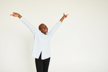 Energetic glad woman with dark skin raising her hands with excitement being thankful to God