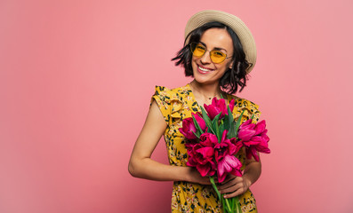 The portrait of a happy excited gorgeous young woman in stylish wear is posing with a freshness bunch of tulips. Mothers day. Women's holidays. Springtime. Wall mural