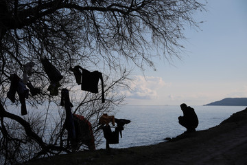 A migrant, who arrived the previous day on a dinghy after crossing part of the Aegean Sea from Turkey, sits next to a tree where clothes are left to dry, near the village of Skala Sikamias, on the island of Lesbos