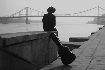 Man in hat and black clothes sits on the river embankment. Near him stands a cover from guitar. Case. Bridge over the river. Back view