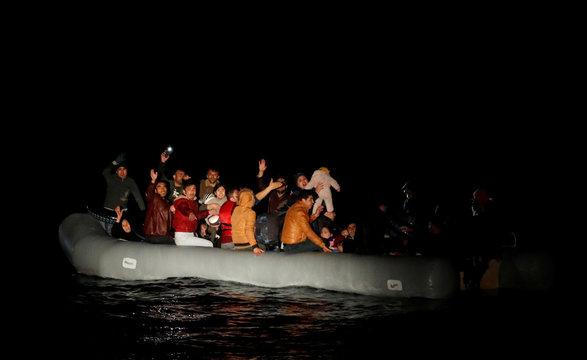 Migrants wave and shout for help following a failed attempt of crossing to the Greek island of Lesbos as a Turkish Coast Guard boat aproaches them on the waters of the North Aegean Sea off the shores of Canakkale