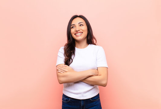 young latin pretty woman feeling happy, proud and hopeful, wondering or thinking, looking up to copy space with crossed arms against flat wall
