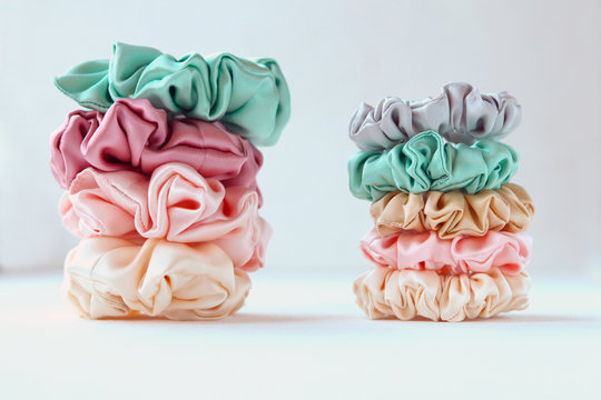 Lot of Colorful silk Scrunchies on white. Luxury Hairdressing tools and accessories. Hair Scrunchies, Elastic HairBands, Bobble Sports Scrunchie Hairband