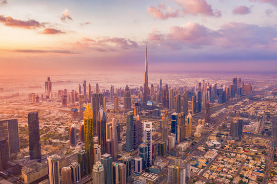 Aerial view of Burj Khalifa in Dubai Downtown skyline and highway, United Arab Emirates or UAE. Financial district and business area in smart urban city. Skyscraper and high-rise buildings at sunset.