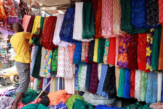 A vendor arranges lace materials for display at his stall in Balogun market in Nigeria's commercial capital, Lagos