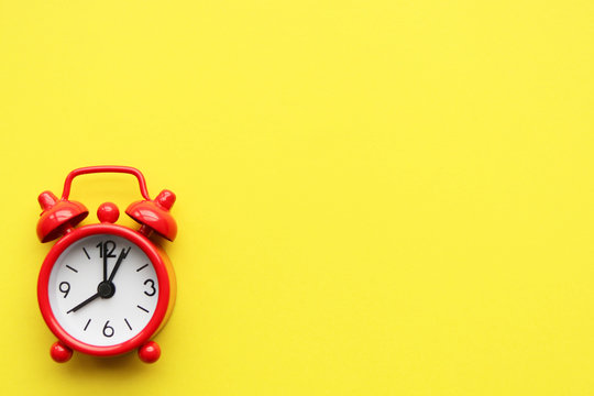 Red alarm clock on a yellow bright background