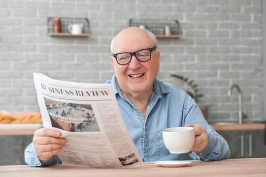 Portrait of elderly man drinking tea while reading newspaper at home