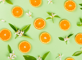 Wall Mural -  Slices of orange fruit and blossom with leaves.