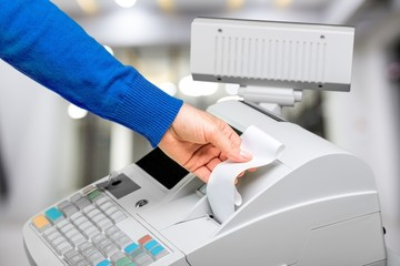 Fototapete - Cash register and worker's hand holding receipt paper