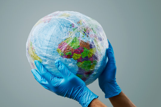 doctor with a world globe wrapped in plastic.