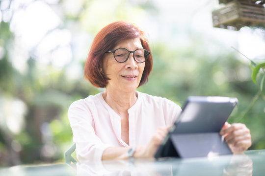 Asian retired woman using computer tablet for social media.Technology and old people concept