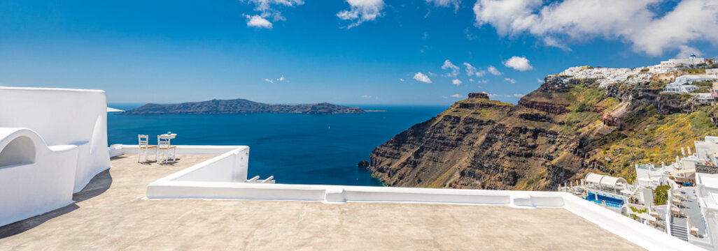 Panoramic travel landscape two chairs on the terrace with sea views. Santorini island, Greece. Travel and vacation background. Best in travel landscape for romantic couple or honeymoon destination. Fa