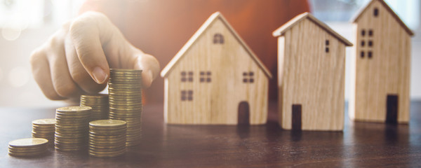 Save to real estate, property owner get money to home concept, small wooden house model on table with hand stacked coins to rent or buy above mentioned residence with cash  to bank agency
