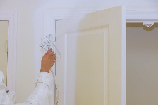 Handyman his hand the painting a spray paint gun, painting wooden door