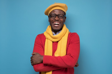 man in red sweater, yellow hat and scarf, glasses smiling looking confident.