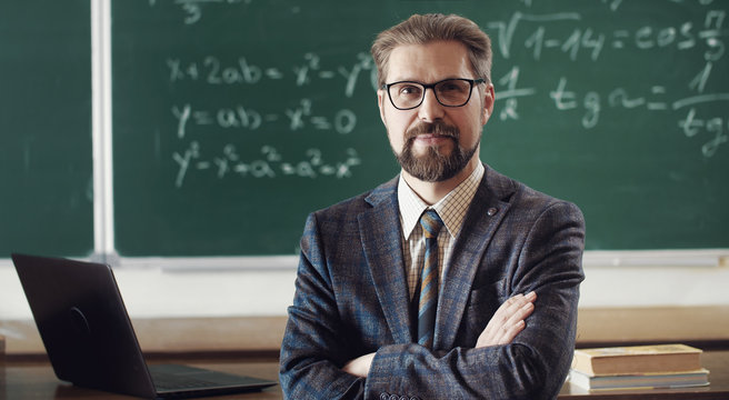 Portrait of smiling mature teacher in classic suit and eyewear standing cross-armed in classroom