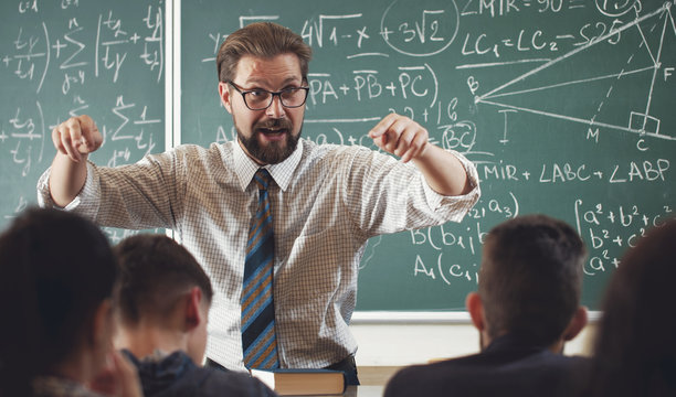 Enthusiastic math teacher explaining subject to students gesticulating with hands in schoolroom