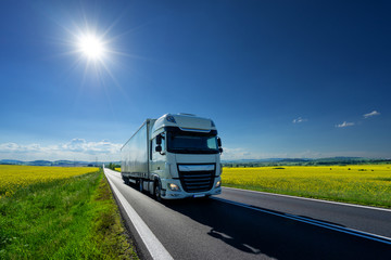 Fotobehang - White truck driving on the asphalt road between the yellow flowering rapeseed fields under radiant sun in the rural landscape